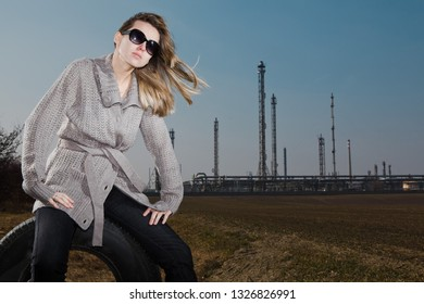 Woman sitting on used tire posing near factory. Strobist lighting used during summer day. Natural skin with no retouches.