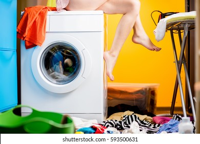 Woman sitting on the washing machine at the loundry. Close-up view on the machine and legs