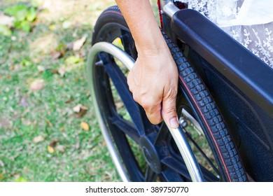Woman Sitting On Wheelchair, Close up Women's hand on wheel