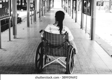 Woman sitting on wheelchair in pathway of park, Black and white concept