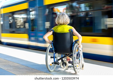 woman sitting on wheelchair on a platform with fast moving train in the background