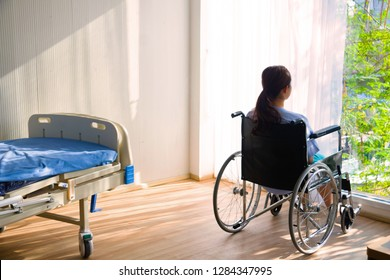 The woman sitting on wheelchair. She is see window with patient bed in hospital.disabled person lonely. Photo concept depression and Patient.