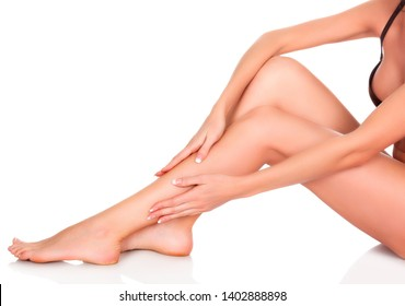 Woman sitting on the white floor and touching her leg by hands, Beauty and skin care concept, isolated on white background