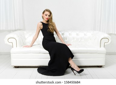 Woman sitting on white leather sofa. Concept of beauty and perfection