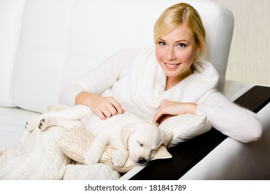 Woman sitting on the white leather sofa with sleeping on the pillow white puppy