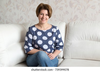 Woman sitting on a white sofa in the room