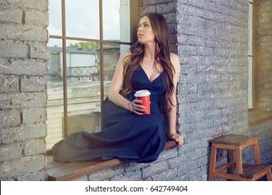 Woman sitting on window Coffee break. Indoor portrait.