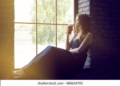 Woman sitting on windowsill. Coffee break. Indoor portrait.
