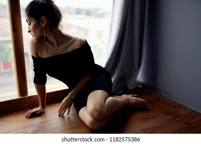 woman sitting on the windowsill and looking out the window