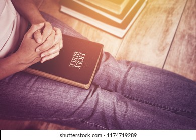 Woman sitting on wood floor while  prays to God over holy bible, christian background copy space