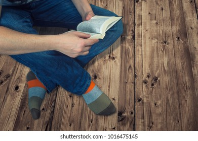 Woman sitting on a wooden floor and reading a book. Education and relaxing concept