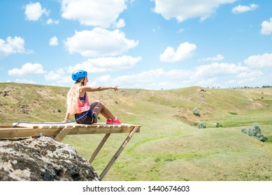 Woman sitting on a wooden ledge on a high mountain and view of the mountain landscape.