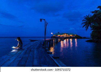 Woman sitting on a wooden pier and reading a book at dusk, using forehead light, Hatta island, Maluku, Indonesia