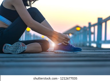 woman sitting on the wooden pier lace tie of the shoe, excercise running and jogging in daily morning healthy lady morning light