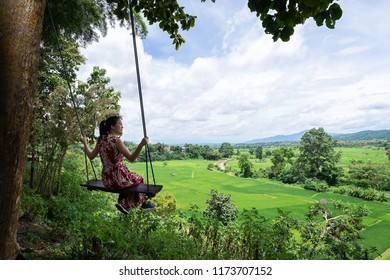 Woman sitting on wooden swing at rice-fields. Lifestyle women relaxing and enjoying swing on the nature field rice,happy and relax in holiday summer.Travel and Summer Concept