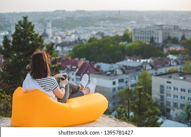 woman sitting on yellow inflatable mattress drinking coffee enjoying sunset over city. copy space