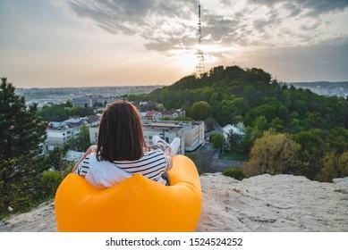 woman sitting on yellow inflatable mattress drinking coffee enjoying sunset over city