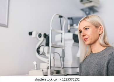 Woman sitting at the optician's office, modern medical equipment in the background. Oculist appointment.
