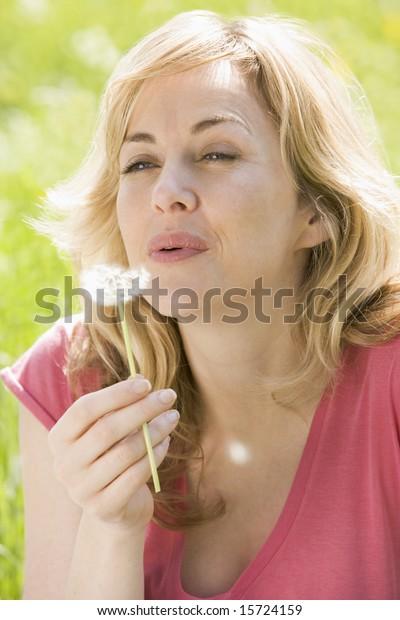 Woman sitting outdoors blowing dandelion head
