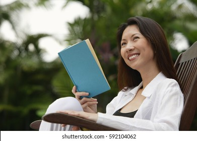 Woman sitting outdoors, reading a book, looking away