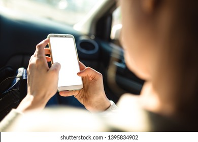 Woman is sitting in the passenger seat of a car and is watching a news feed of one of the social networks on her smartphone