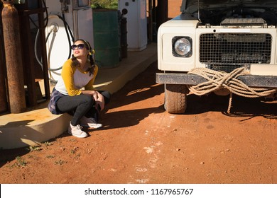 Woman sitting at petrol pump station on a sunny day