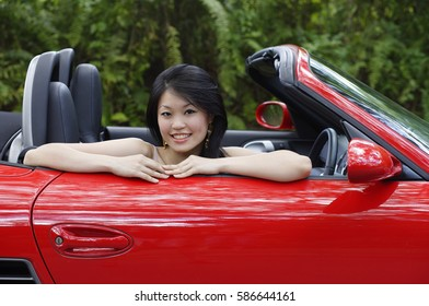 Woman sitting in red sports car, smiling at camera, portrait