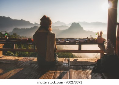 woman sitting and relaxing in Thai restaurant with enjoying sunrise