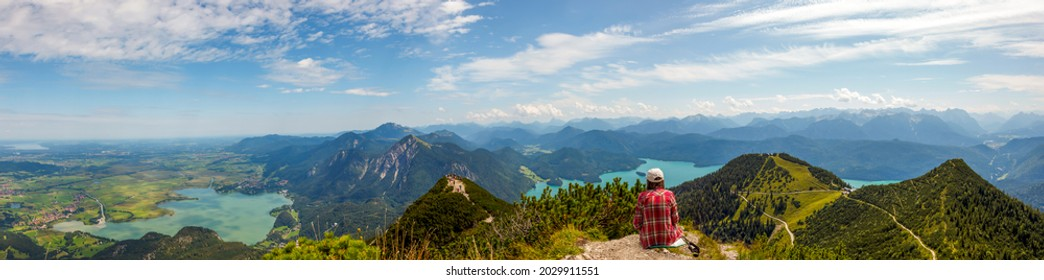 Woman sitting and relaxing at top of Mountain Herzogstand after hiking. looking at the spectacular bavarian Prealps mountains panorama with Lakes (Kochelsee, Walchensee) Europe, Germany