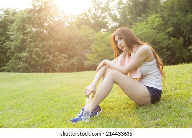 Woman sitting rest after exercise. Hand holding a bottle of water and sit On the lawn.