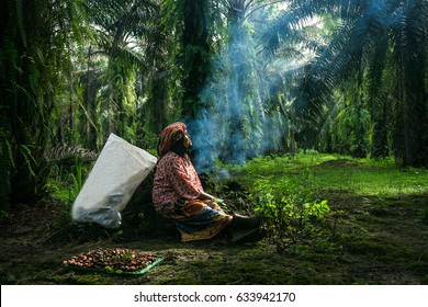 Woman is sitting and resting under the oil palm tree