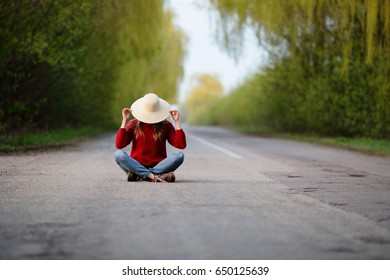 Woman sitting in road, resting, traveler, covers face with straw hat , nature