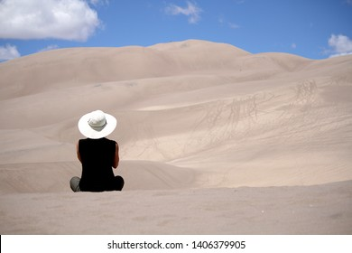 A woman sitting in the sand at the Great Sand Dunes National Park, Colorado.