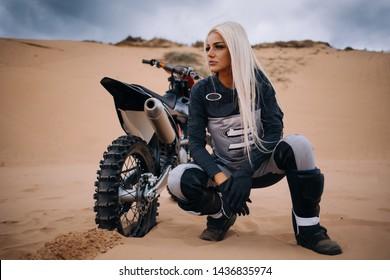 Frau sitzt in der Sanddüne bei einem Kreuz-Motorrad in der Wüste