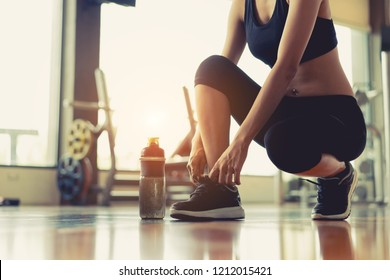 Woman sitting shoelaces with protein shake at fitness gym after running exercise workout for cardio and muscle building.