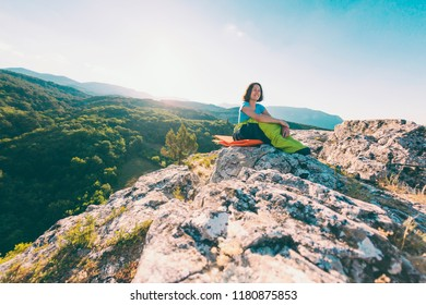 A woman is sitting in a sleeping bag on top of a mountain. A smiling girl rests after a climb. The brunette sits on a self inflating mat on the background of the mountains and the setting sun.