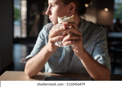 Woman is sitting in small cafe and holding tortilla wrap before eating, looking aside. Gourmet conception.
