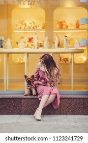 woman is sitting with a small dog in the city near the shop window