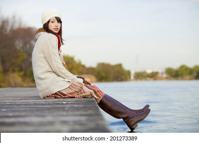 A Woman Sitting And Smiling On The Riverside