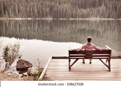 Woman Sitting in Solitude by Calm Lake