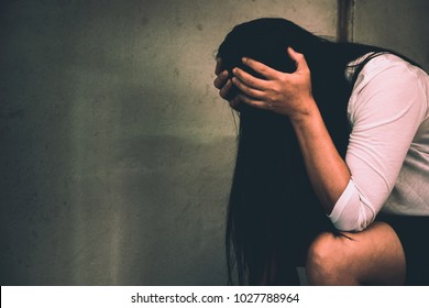 Woman sitting strain ,unhappy In the corner of the room, domestic violence, abuse and people concept.