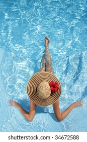 Woman sitting in a swimming pool in a large sunhat