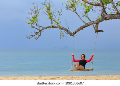 Woman sitting swing hanging on a branch at sandy beach
