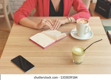 A woman is sitting at a table in a cafe with a spare book. On the table stands a mug of cappuccino, a telephone and a matcha tea. Negotiation concept in co working place. Living coral concept