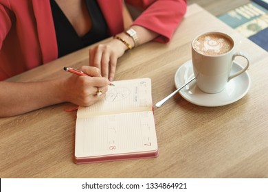 A woman is sitting at a table in a cafe with a spare book. On the table stands a mug of cappuccino. Negotiation concept in co working place. Living coral concept
