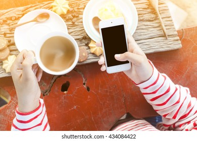 Woman sitting at a table with a coffee using smartphone.