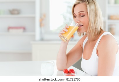 Woman sitting at a table drinking orange juice in the kitchen