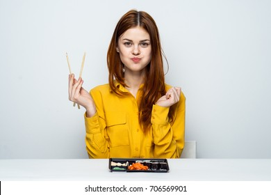 woman sitting at a table eating sushi, rolls, wasabi, asia, japan, pink ginger, rolls
