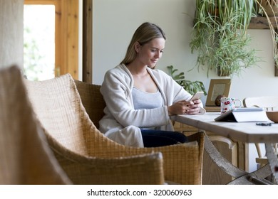 Woman sitting at a table in her home using a smartphone