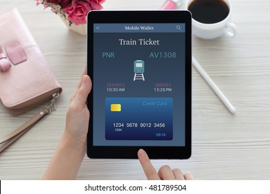 woman sitting at the table and holding tablet computer with online train ticket